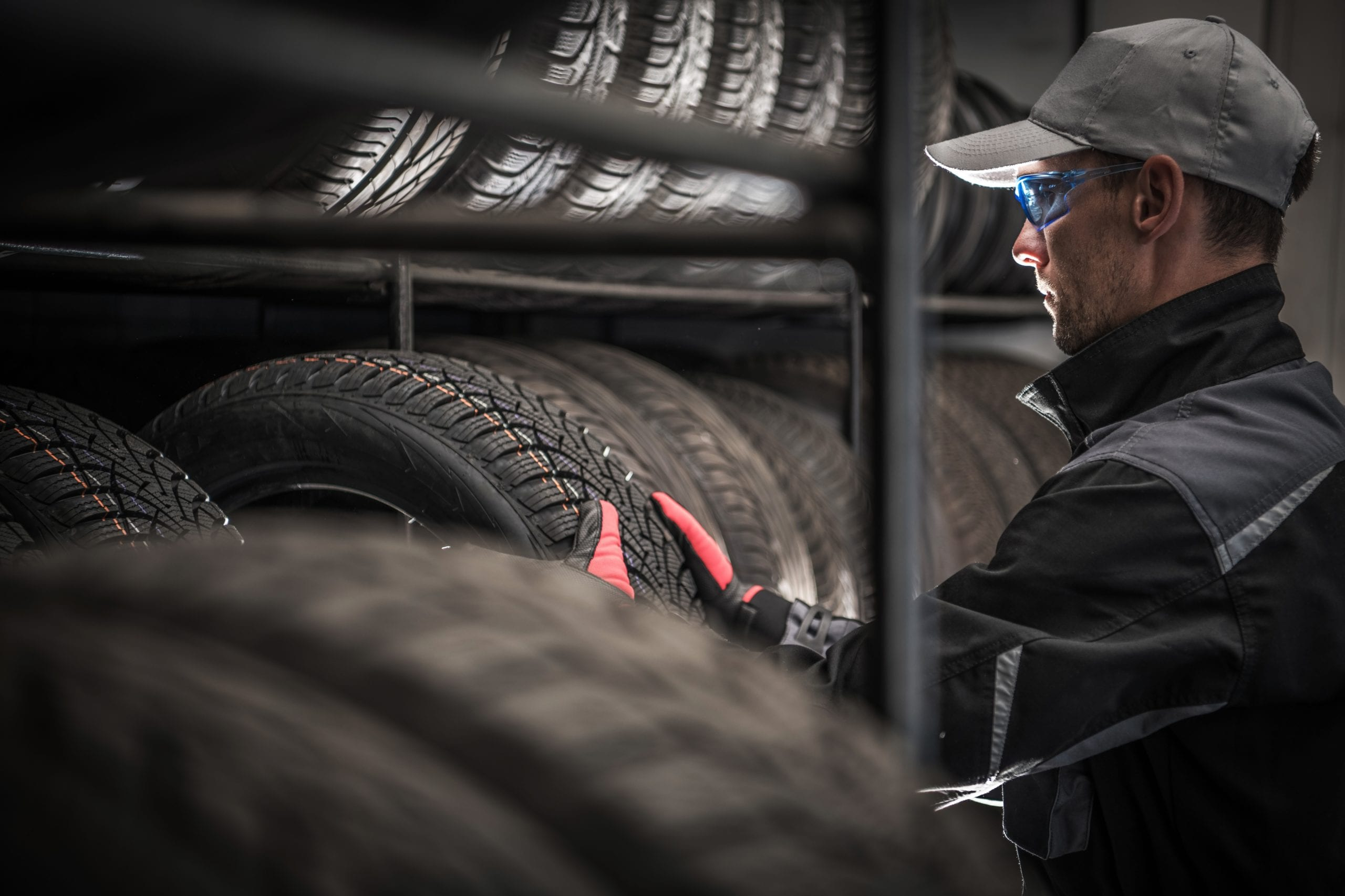 Choosing Right Car Tires For the Season. Vulcanization and Tire Sales Shop Caucasian Worker in His 30s. Automotive Theme.